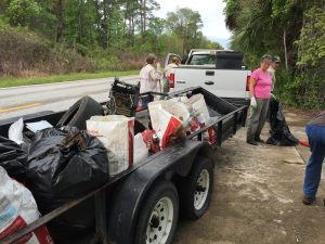 Volunteers load bags of trash into a trailer attached to a white pickup truck